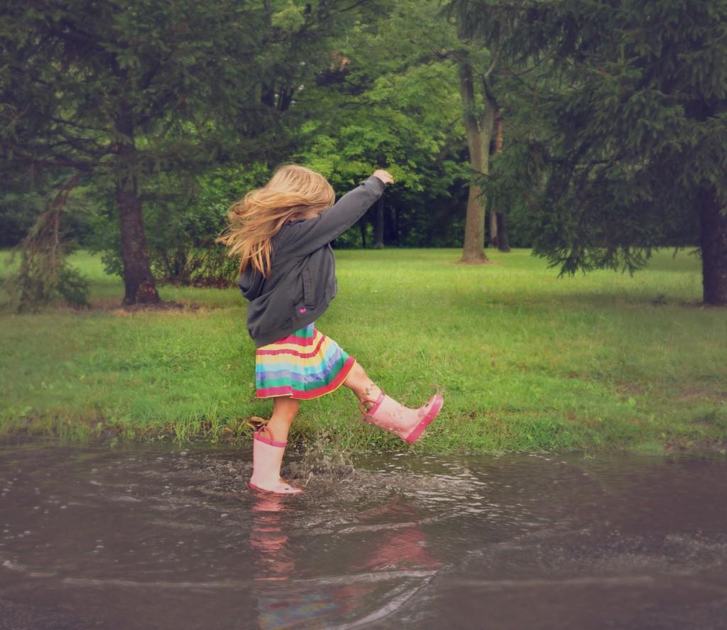Glück Child Splashing in Dirty Mud Puddle